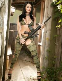 Hot brunette Sophie Dee poses with an automatic rifle before rough anal sex