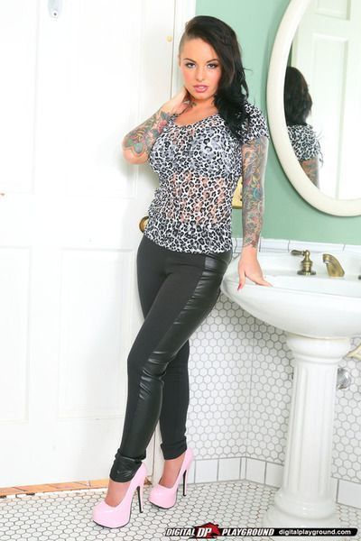 Amazingly sexy brunette slowly uncovering her tattooed curves in the bathroom