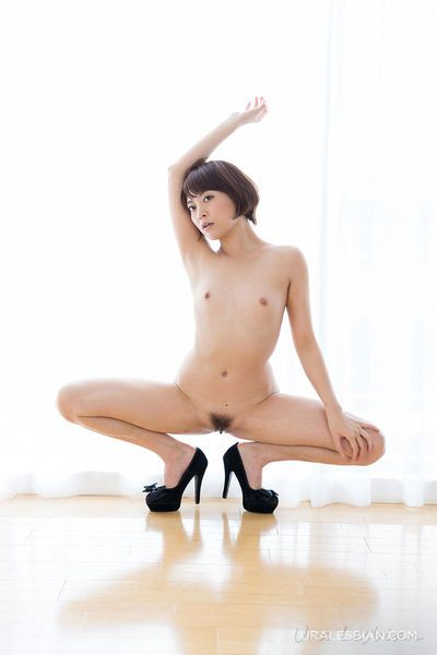 Naked Oriental girls with flat chests model together in high heeled shoes