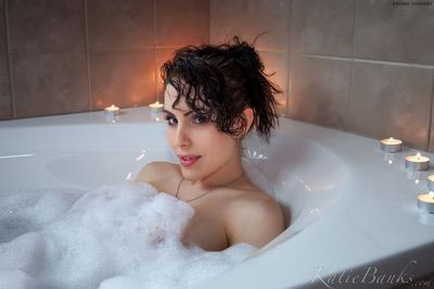Brunette amateur Katie Banks showing her pink pussy in tub by candlelight