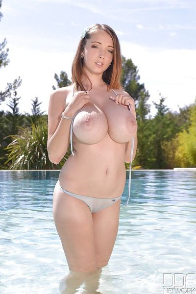 Wet chick Lucie Wilde freeing huge natural tits from bikini in pool