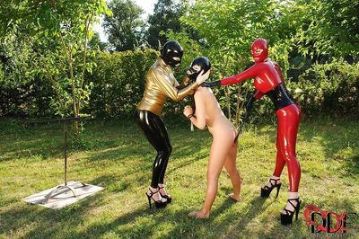 BDSM mistresses in latex suits have some fun with their female pet outdoor