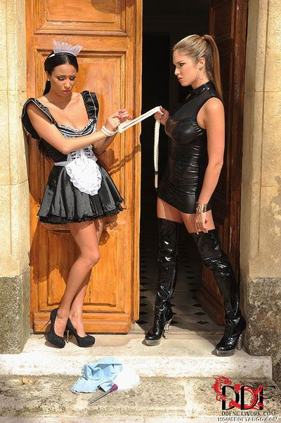Tall latex boot adorned Domme using uniform clad maid in BDSM lezdom scene