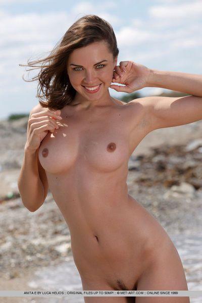 Brunette European beach girl Anita E showing firm tits & bald pussy on knees