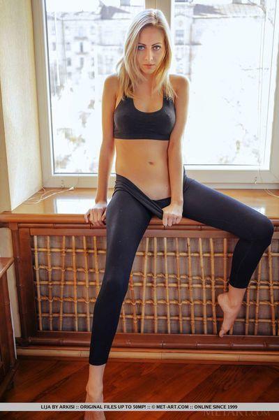 Teen babe slides yoga pants over long legs during glamour shoot
