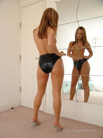 Pretty carla poses topless in front of a mirror in black latex p