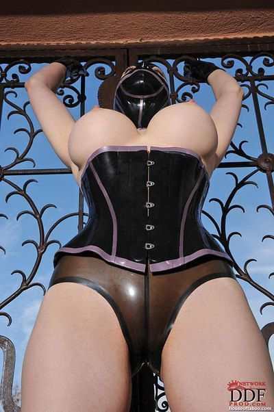 Busty babe on high heels Lucy Latex posing in fetish outfit